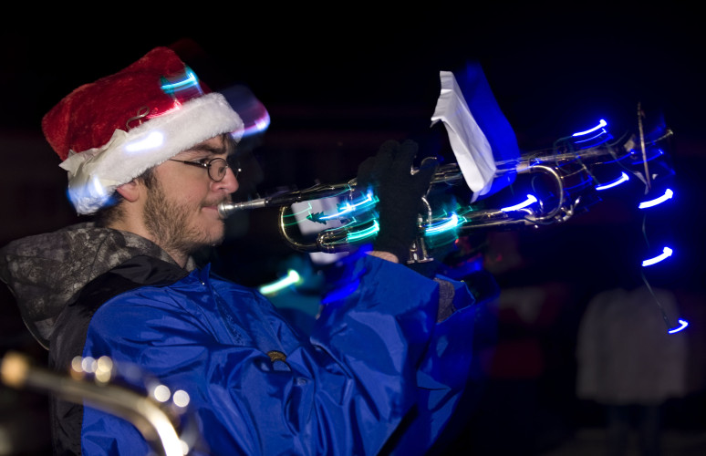 Central High School band member Brandon Trump, 15, plays the trumpet as the band marches up Stoney Creek Boulevard during the Edinburg Christmas parade held on Thursday night. The Central band also performed at the town's tree lighting  ceremony, which followed the parade.  Rich Cooley/Daily